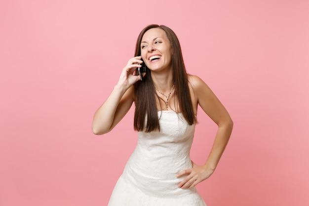 Retrato de mujer alegre en vestido blanco hablando por teléfono móvil recibiendo felicitaciones
