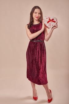 Retrato de mujer alegre en vestido rojo con caja de regalo