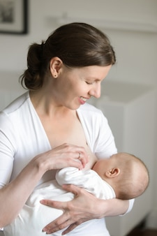 Retrato de una mujer amamantando a un niño, en sus manos