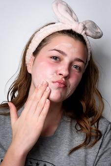 Retrato de mujer aplicando crema en un rostro limpio y fresco en gris