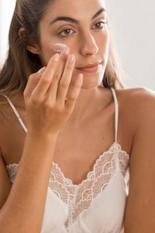 Retrato de mujer aplicando crema en el rostro