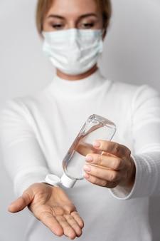 Retrato de mujer aplicando gel de lavado para manos