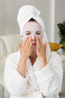 Retrato de mujer aplicando mascarilla facial