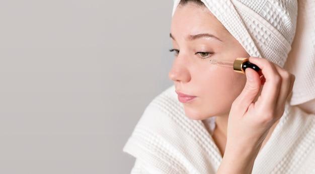 Retrato mujer aplicando suero facial