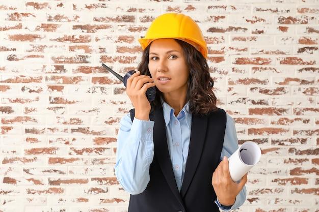 Retrato de mujer arquitecta con transmisor de radio portátil contra la pared de ladrillo