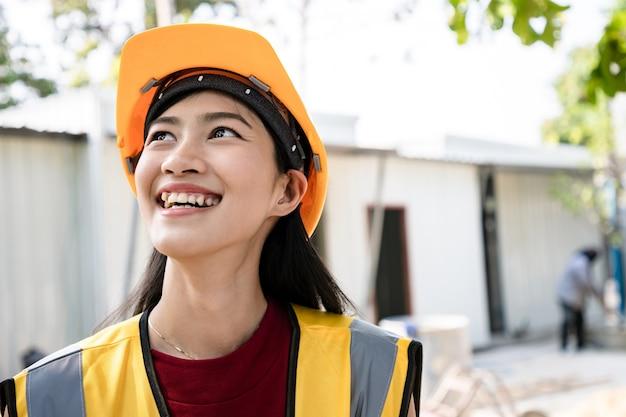 Retrato de mujer arquitecto de pie y sonrisa brillante después de comprobar el proyecto y el informe estadístico en el sitio. vista posterior de la propiedad de la casa con trabajador.
