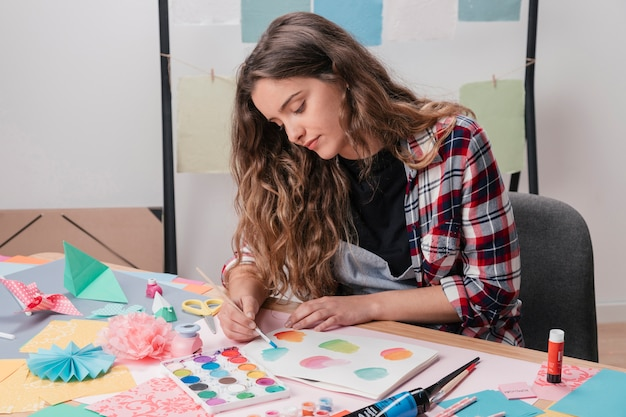 Retrato de mujer artista pintando sobre papel blanco