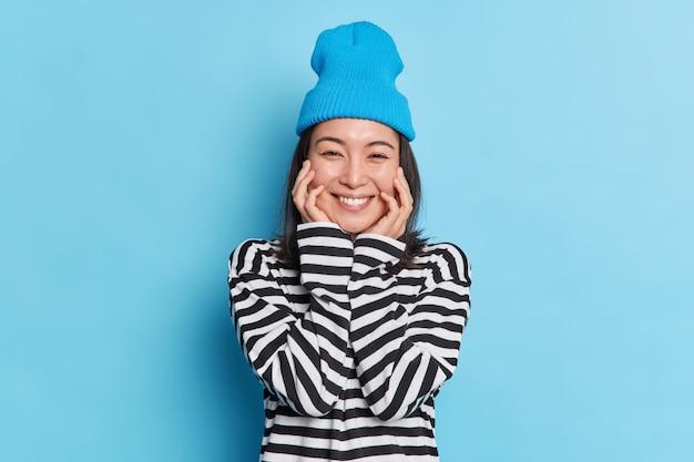 Retrato de mujer asiática alegre de aspecto agradable mantiene las manos en las mejillas sonríe suavemente viste suéter de rayas elegante sombrero expresa emociones sinceras