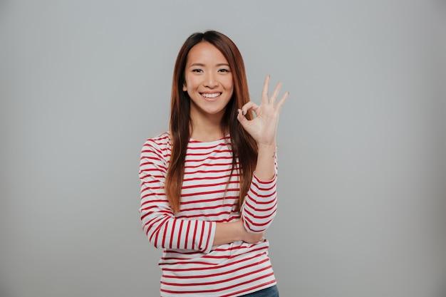 Retrato de una mujer asiática alegre que muestra gesto bien