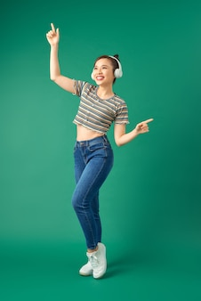 Retrato de mujer asiática alegre en ropa casual bailando y escuchando música con auriculares en verde.