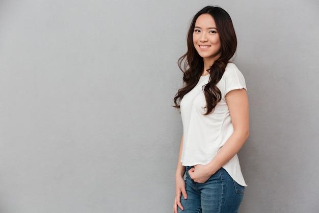 Retrato de mujer asiática atractiva con cabello rizado oscuro posando con la mano en el bolsillo y una sonrisa sincera, aislado sobre la pared gris