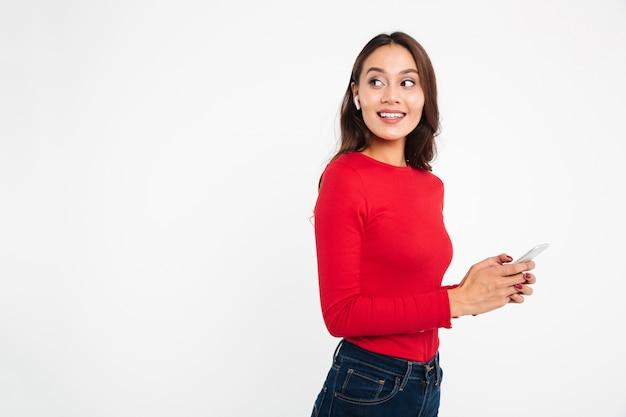 Retrato de una mujer asiática contenta alegre en auriculares