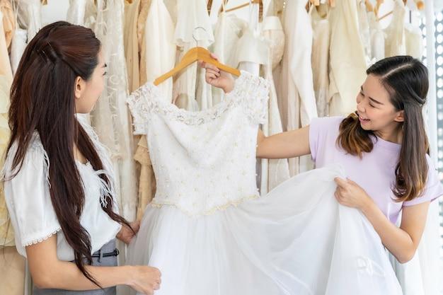 Retrato de mujer asiática elegir vestido en una tienda con asistente de sastre.