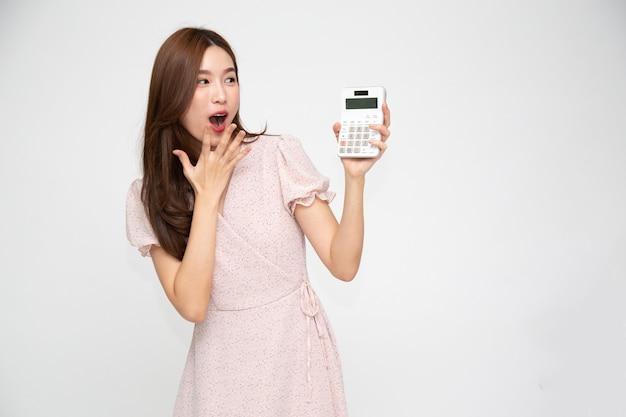 Retrato de mujer asiática emocionada sosteniendo calculadora aislado sobre fondo blanco.