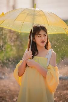 Retrato de mujer asiática feliz celebración paraguas amarillo en la mano lloviendo