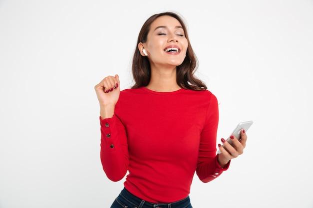 Retrato de una mujer asiática feliz contenta en auriculares