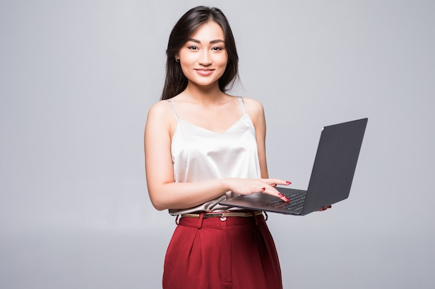 Retrato de una mujer asiática feliz que trabaja en la computadora portátil aislada sobre la pared blanca