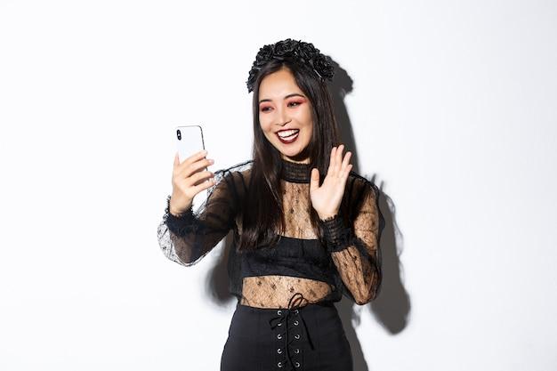 Retrato de mujer asiática hermosa y elegante en vestido de encaje gótico saludando a la cámara del teléfono inteligente durante la videollamada, de pie sobre fondo blanco.
