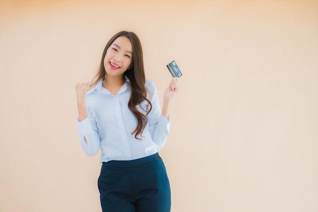 Retrato de mujer asiática hermosa joven con tarjeta de crédito