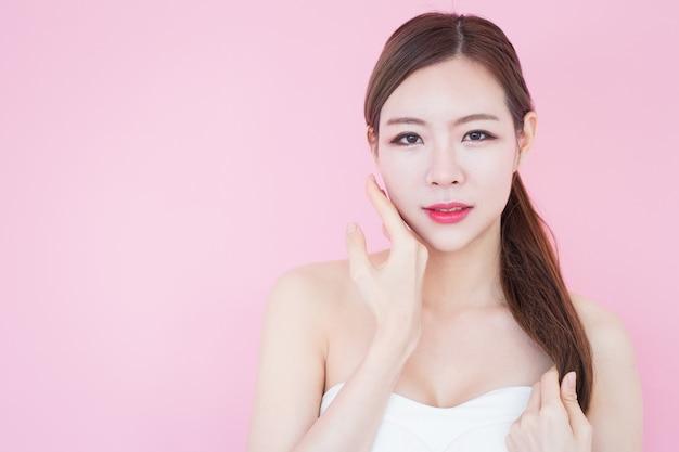 El retrato de la mujer asiática hermosa joven toca su cara limpia y fresca de la piel