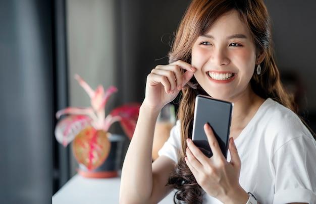 Retrato de la mujer asiática hermosa que usa el teléfono móvil en el café