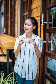 El retrato de la mujer asiática hermosa se relaja en el café