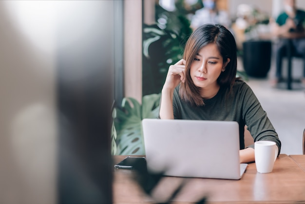 Retrato de mujer asiática inteligente freelance en línea trabajando con una computadora portátil en un espacio de trabajo compartido