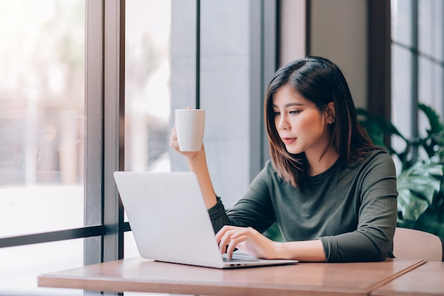 Retrato de mujer asiática inteligente independiente que sostiene una taza de café y trabaja en línea con una computadora portátil en un espacio de trabajo compartido
