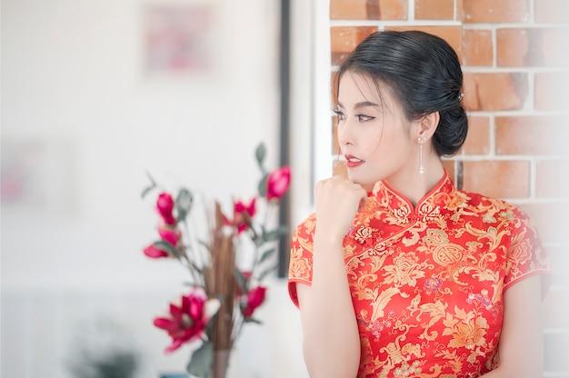 Retrato de la mujer asiática joven en cheongsam tradicional del vestido rojo