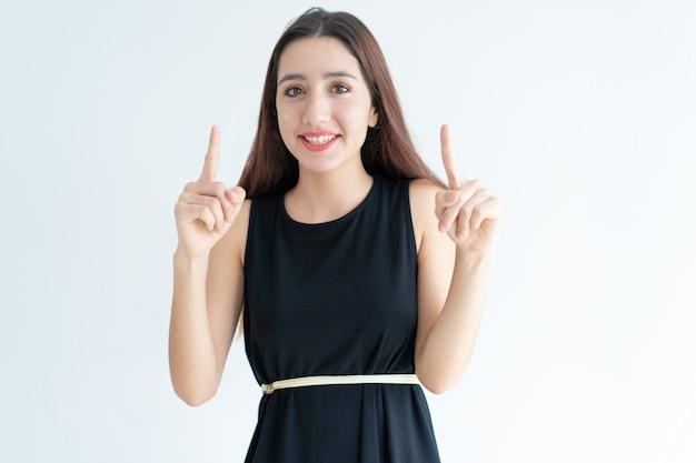 Retrato de mujer asiática joven feliz apuntando hacia arriba y sonriendo