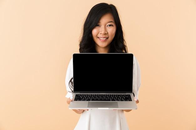 Retrato de una mujer asiática joven feliz espacio aislado, de pie, mostrando portátil con pantalla en blanco