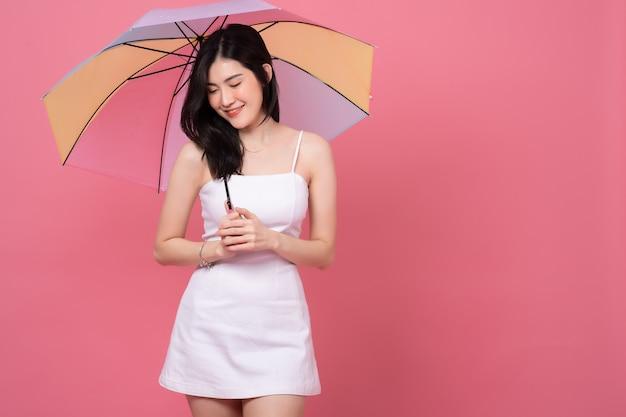 Retrato de mujer asiática joven feliz con vestido blanco sosteniendo paraguas, sonriendo en rosa