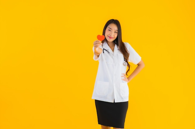 El retrato de la mujer asiática joven hermosa del doctor muestra el corazón rojo