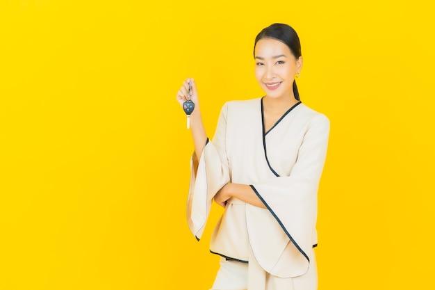 Retrato de mujer asiática joven hermosa con la llave del coche en la pared amarilla