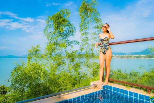 Retrato de mujer asiática joven hermosa que se relaja alrededor de la piscina al aire libre con vista al mar