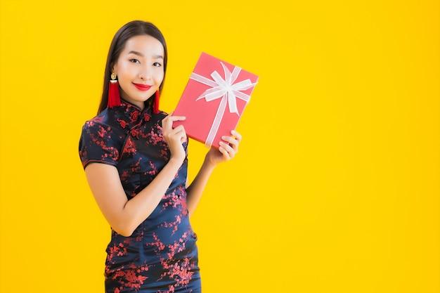 El retrato de la mujer asiática joven hermosa viste el vestido chino y sostiene la caja de regalo roja