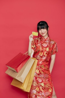 Retrato de mujer asiática joven linda usar vestido chino con una bolsa de compras y tarjeta de crédito para el año nuevo chino en una pared roja
