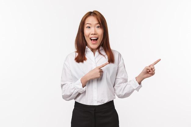 Retrato de mujer asiática joven maravillada emocionada en camisa y falda, señalando con el dedo a la derecha sonriendo cámara con expresión de entusiasmo entusiasmado, hablando de nuevo producto increíble