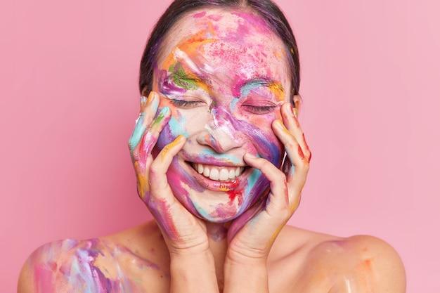 Retrato de mujer asiática joven morena sonríe agradablemente mantiene ambas manos en las mejillas se encuentra con los ojos cerrados tiene la cara manchada por pinturas al óleo de colores