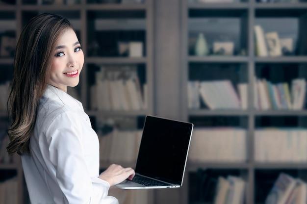Retrato de la mujer asiática joven que sostiene el ordenador portátil