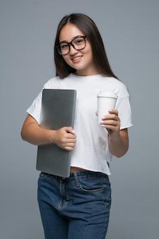 Retrato de una mujer asiática joven satisfecha sosteniendo una taza de café y una computadora portátil mientras camina y mira a la cámara sobre fondo gris