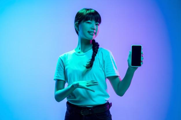 Retrato de mujer asiática joven sobre fondo de estudio azul-púrpura degradado en luz de neón. concepto de juventud, emociones humanas, expresión facial, ventas, publicidad. preciosa modelo morena.