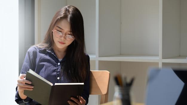 Retrato de mujer asiática leyendo un libro en la biblioteca