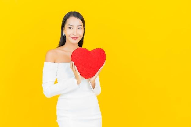 Retrato de mujer asiática de negocios joven hermosa con almohada en forma de corazón en la pared de color amarillo