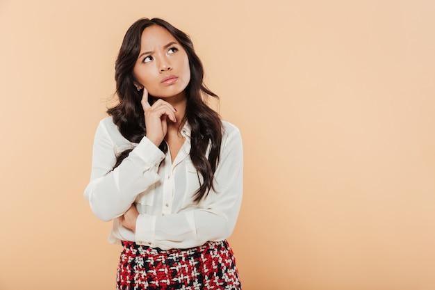 Retrato de una mujer asiática pensativa de pie