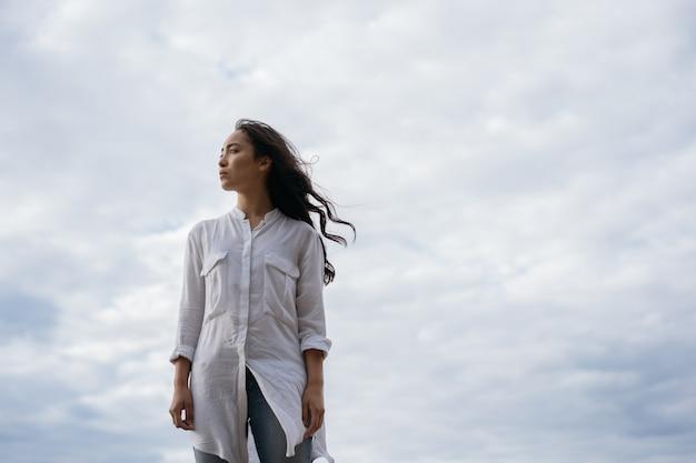 Retrato de mujer asiática pensativa respirando aire fresco