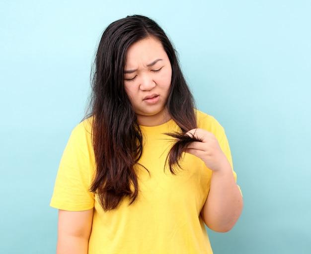 Retrato mujer asiática con problemas de cabello - cabello quebradizo, dañado, seco, sucio y perdido, sobre fondo azul en estudio.