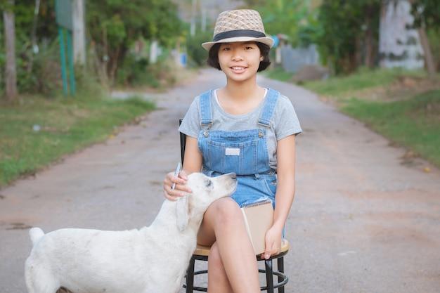 Retrato de la mujer asiática que sonríe afuera con el libro y el perro