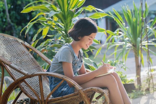 Retrato de la mujer asiática que sonríe afuera con el libro
