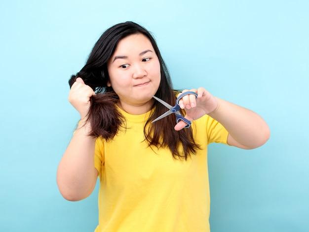 Retrato la mujer asiática quiere cortar su cabello dañado, sobre fondo azul en estudio.